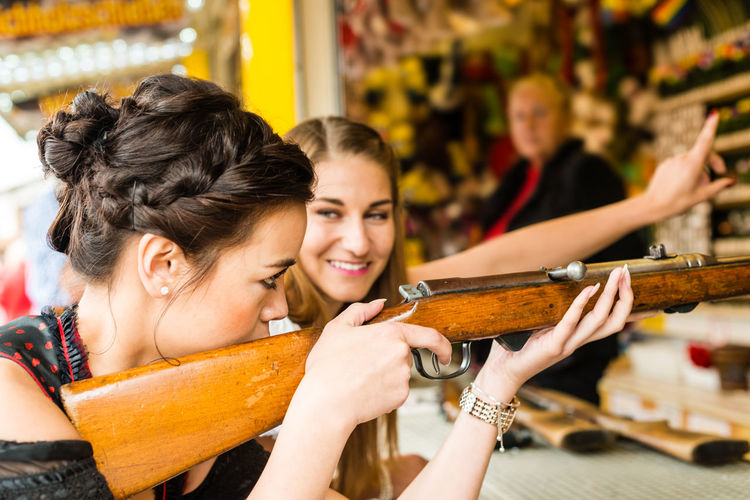 Happy Woman Target Shooting With Gun At Oktoberfest