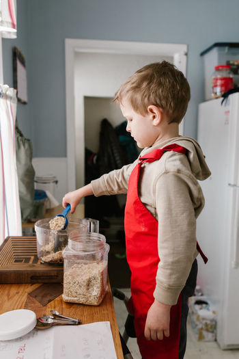 Measuring Baking Boys Child Baking Child Cooking Child In Kitchen Childhood Day Food Processor Holding Indoors  Oats One Person People Real People Red Apron Side View Standing