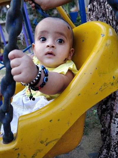 Cute Girl Sitting On Swing In Playground