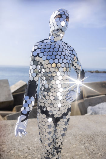Man wearing shiny costume against sky