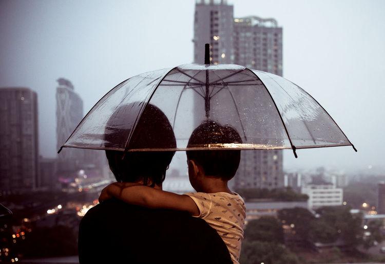 Rear view of man holding umbrella in city during rainy season