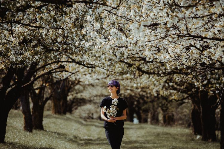Full length of woman standing on cherry blossom