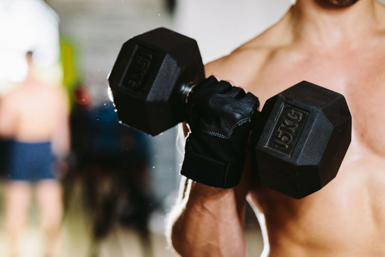 Midsection Of Shirtless Man Exercising With Dumbbell In Gym