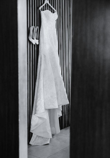 Wedding dress hanging next to shoes during the preparation of the event, black and white photo