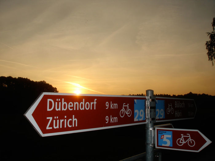 Close-up of german text sign post against sunset sky