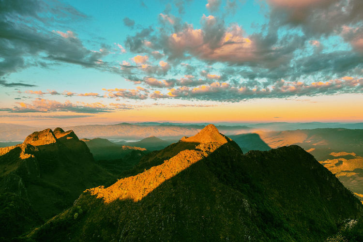 Scenic view of mountain against cloudy sky during sunset
