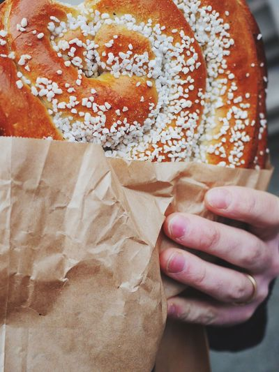Cropped Image Of Hand Holding Pretzel With Wax Paper