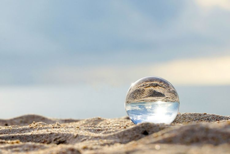 Close-up of crystal ball on beach against sky