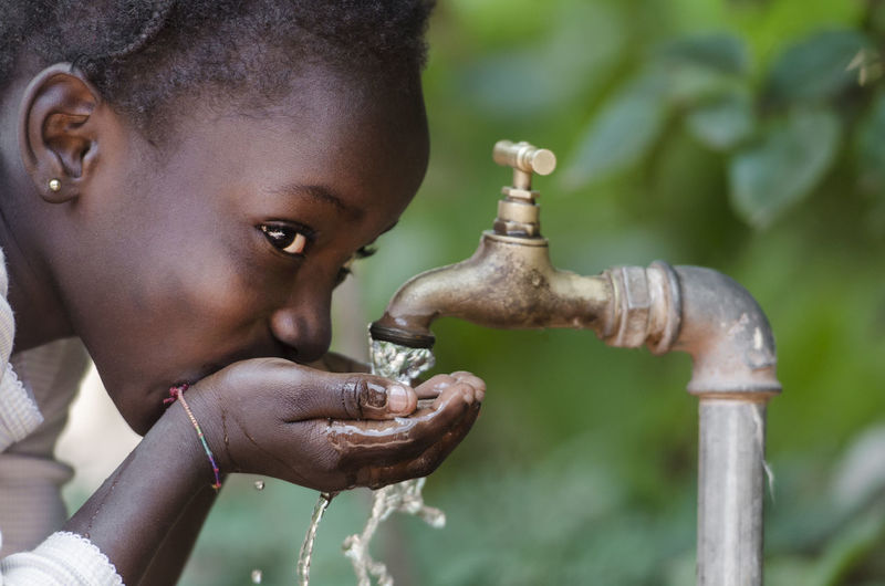 Close-up portrait of woman drinking water from faucet