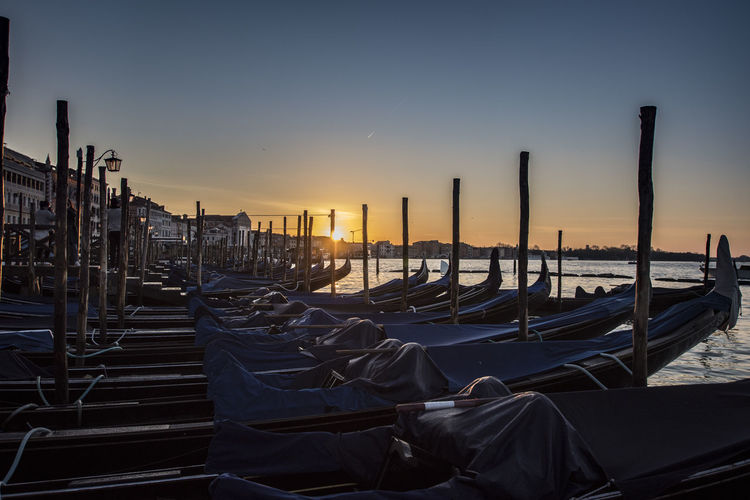 Gondola - Traditional Boat Moored In San Marco Canal Against Sky During Sunset