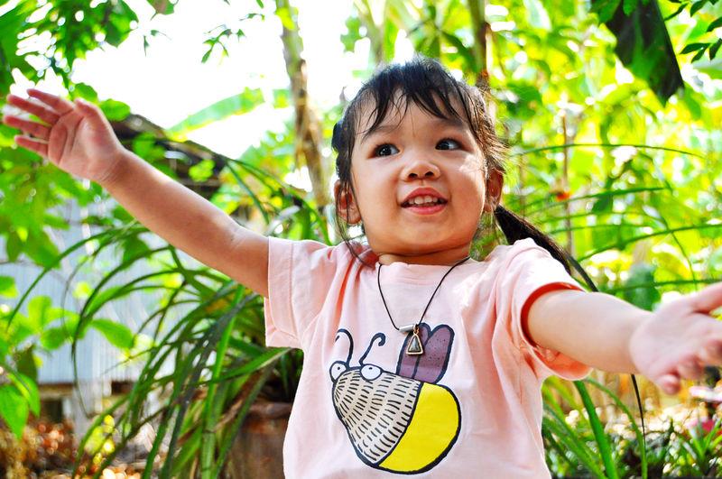 Portrait of smiling girl against plants