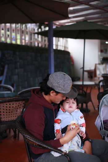 Father and son sitting on seat at restaurant