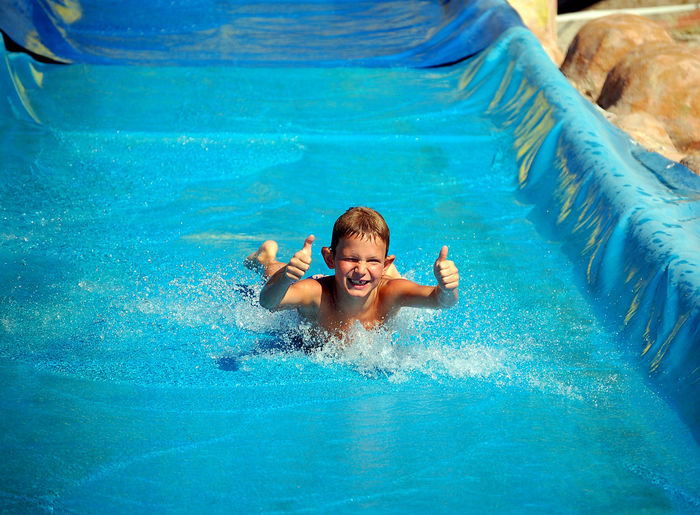 Portrait Of Happy Boy Showing Thumbs Up Sign While Sliding At Water Park