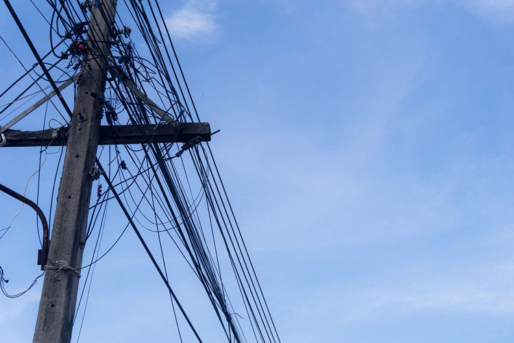 Close up old electricity poles with telephone lines many. under sky background.
