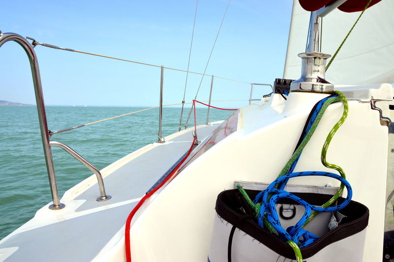Rope on sailboat in sea against sky during sunny day