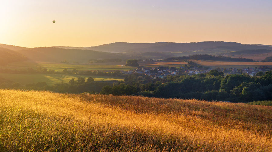 Panoramic view of golden grass, countryside and sun setting over rolling hills