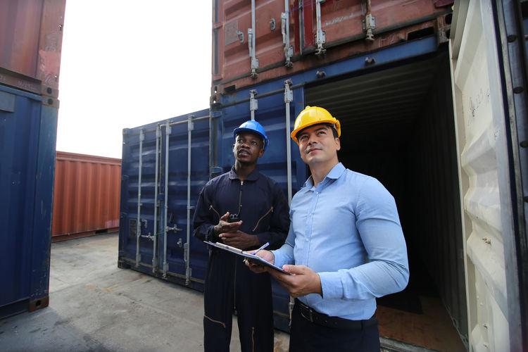 Men standing against cargo container