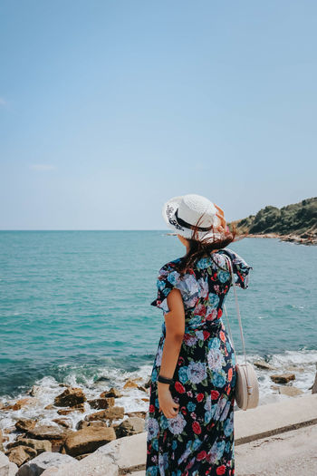 Person looking at sea against sky