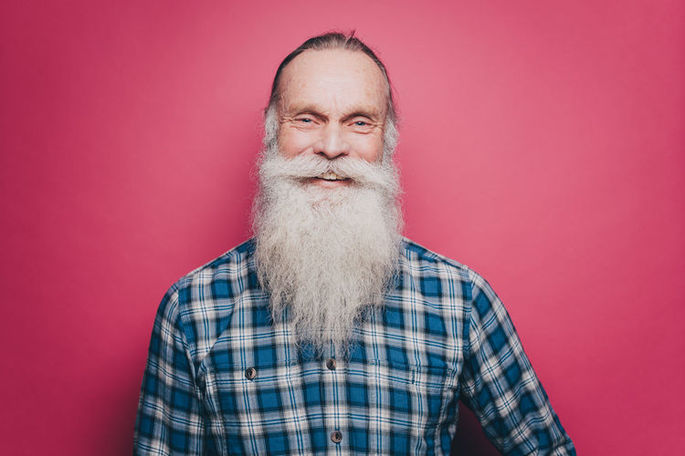 Portrait of man against red background