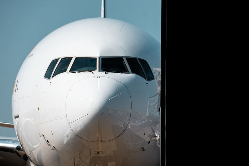 Close-up of airplane on runway against clear sky