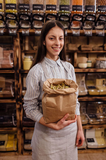 Portrait of smiling shopkeeper in package free grocery store. Cheerful shop assistant holding paper bag full of dried herb leaves in zero waste shop. Zero Waste Plastic Free Package Shop Store Raw Food Food Refill Organic Shopping Business Homemade Horizontal Grocery Bulk Interior Container Dispenser One Person Portrait Shopkeeper Shop Assistant Bio Eco