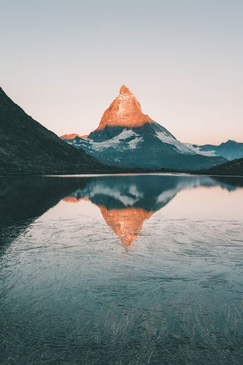 Impressive sunrise at Matterhorn mountain in Switzerland Alps Calm Lake Landmark Landscape Light Matterhorn  Morning Morning Glow Morning Light Mountain Mountain Range Nature Outdoors Peaceful Pure Beauty Reflection Schweiz Sunrise Swiss Switzerland Toblerone Tranquil Scene Tranquility Travel The Great Outdoors - 2017 EyeEm Awards