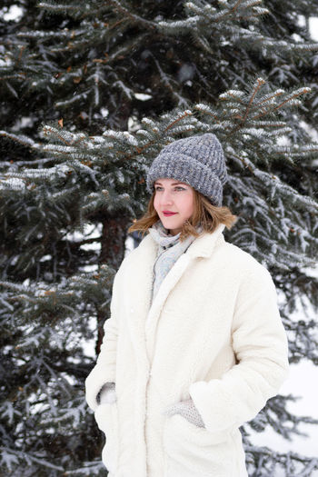 Young woman standing on snow covered tree
