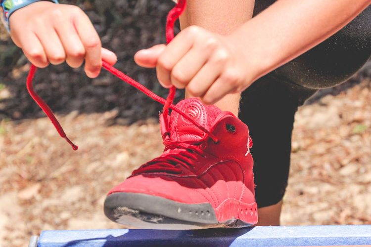 young boy tying his shoelaces on red sneakers Child Tying Shoelaces Sneakers Boys Shoelace Human Body Part Human Hand Hand Offspring Childhood Child Red Leisure Activity Holding Body Part Close-up Lifestyles Focus On Foreground Day Finger Outdoors 2018 In One Photograph