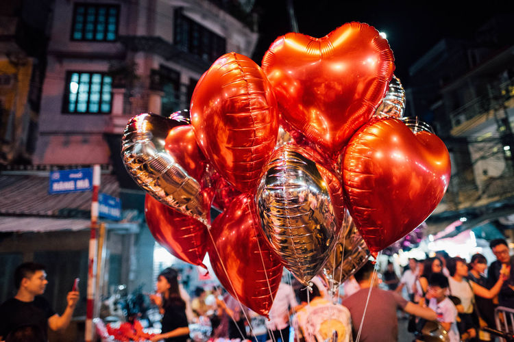 Close-up of heart shaped balloons in city at night