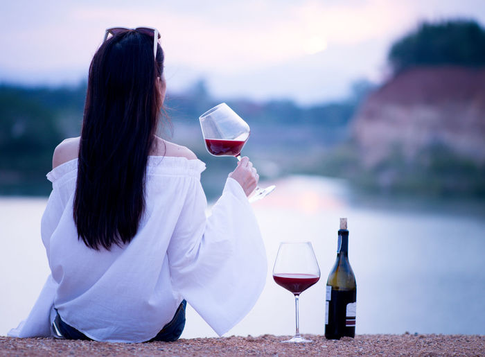 Rear View Of Woman Having Red Wine Against Lake