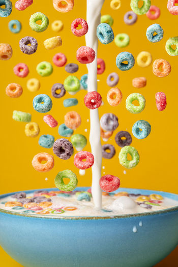 Dropping cereals and pouring milk into a blue bowl, on an orange background. preparing breakfast.