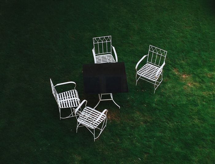 High angle view of empty chairs and table on field