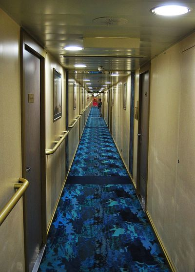 The view down a long corridor on a cruise ship. Cabin Doors Cabins  Ceiling Corridor Cruise Ship Diminishing Perspective Illuminated Long Narrow Ocean Liner Passage Passageway Vanishing Point