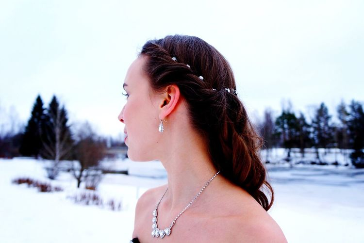 Beautiful woman looking away while standing on snow covered field against sky