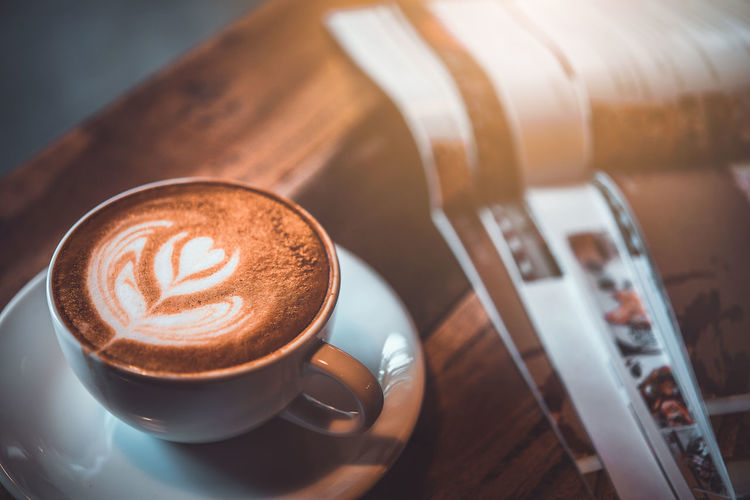 Cup of Latte on the table with magazine at coffee shop, vintage warm tone Aroma Art Attractive Background Barista Beverage Black Book Breakfast Brown Business Cafe Caffeine Cappuccino Classic Closeup Coffe Coffee Cup Design Drink Espresso Foam Food Fresh Freshness Hipster Hot Latte Magazine Milk Morning Mug Pouring Professional Retro Shape Shop Style Table Top View Vintage Wood Food And Drink Coffee - Drink Refreshment Still Life Coffee Cup Hot Drink