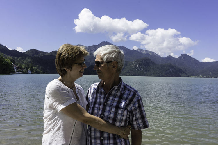 Happy Senior Couple Embracing By Lake Against Sky