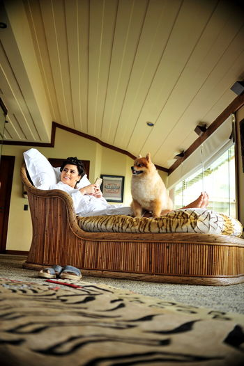 Woman Relaxing With Dog On Bed At Home