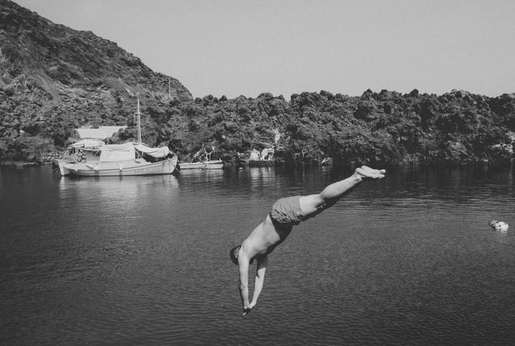 Black & White Black And White Black And White Photography Monochrome Photography Blackandwhite Blackandwhite Photography Boat Calm Clear Sky Day Island Jump Jumping One Person Outdoors Santorini Santorini, Greece Sea Seaside Summer Tranquil Scene Vacations Volcano Water Adventure Club Black And White Friday