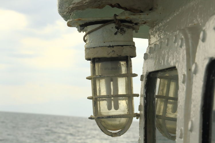 Close-up of light bulb on boat against sky