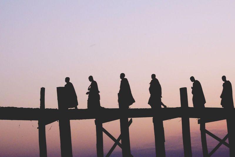 Monk Walking On Pier Against Sky