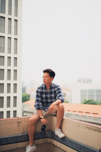 Young man with camera sitting on railing against clear sky