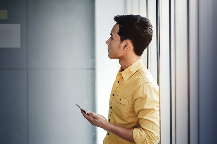 Young Businessman Standing by the Window in Office. Holding Smartphone and looking at the Wall One Person Side View Wireless Technology Technology Communication Standing Young Adult Business Person Looking Waist Up Young Men Connection Business Mobile Phone Holding Indoors  Men Adult Real People Profile View Contemplation Indoors  Asian  Businessman