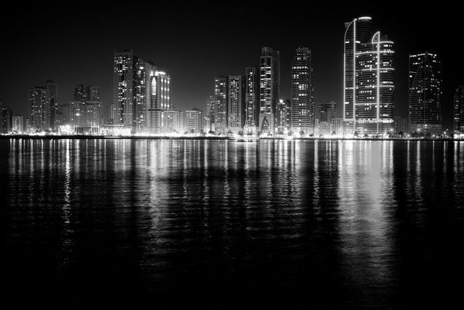 Cliche but i still thirst more for the view Reflection Water City Architecture Sky No People Waterfront Outdoors Sea Skyscraper Built Structure Building Exterior Night Cityscape Illuminated Photography Blackandwhite Sillhouette Architecture Nightphotography Monochrome Urban Skyline UAE Sharjah Middle East