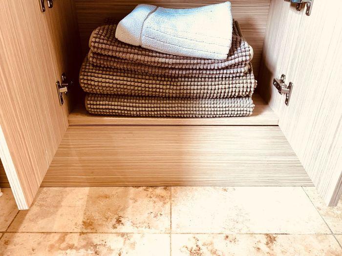 Bath mats folded in a cupboard Bath Mat Bathroom Cupboard High Angle View Clothing Flooring Indoors  Day Adult Tiled Floor Lifestyles