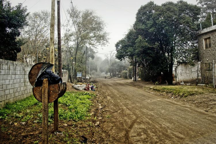Dirt road by trees in village