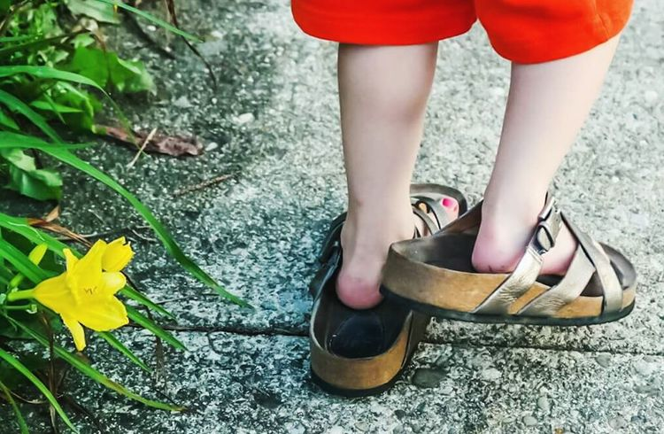The little boy hopes to fill his mother's shoes. Kids Playing Dress-up Shoes Whimsical Summer Fun Boys Mother And Son Sidewalk Feet Cute Son Sandals Lillies Yellow Flower Too Big Boys Like Paint Too