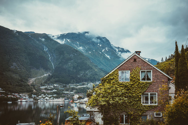 Building by mountains against sky