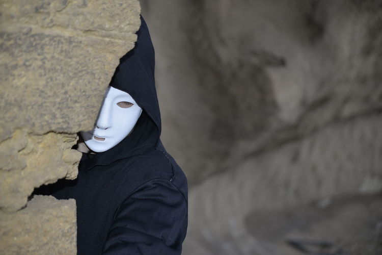 Midsection of person wearing mask standing on rock