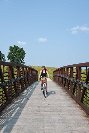 Man riding bicycle on footbridge against sky