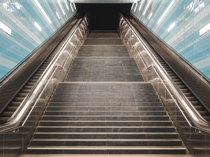 Low angle view of staircase amidst escalators at subway station